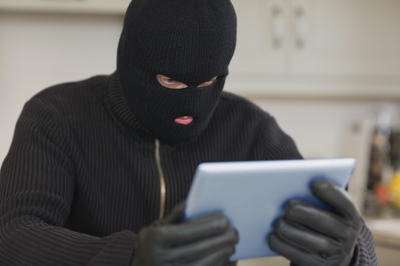 Burglar holding tablet pc in kitchen photo