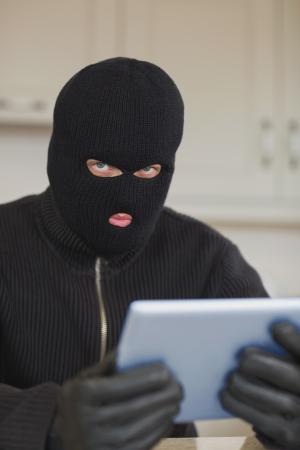 burgler: Suspicious burgler holding tablet pc in kitchen