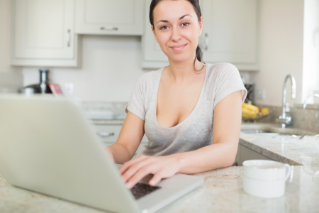 Smiling woman using laptop in kitchen photo
