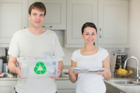 Couple holding recycling bin and newspapers in kitchen photo