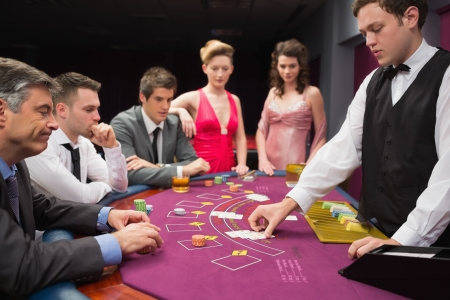 People looking at dealer dealing blackjack cards in the casino Reklamní fotografie