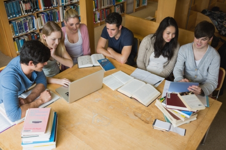 bookshelf digital: Group of students sitting at a table in a library while learning and using tablet and laptop