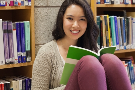 Student sitting in a library on the floor while holding a book and smiling photo