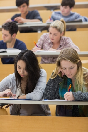 student in class: Students studying in a lecture hall with one girl using tablet pc in college