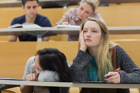 Demotivated students sitting in a lecture hall with one girl napping in college Stock Photo