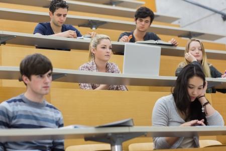 Schüler hören in einem Hörsaal in der Hochschule und Notizen Standard-Bild - 20517440