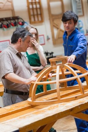 Studenti e un insegnante in piedi in una classe di falegnameria e parlando di una struttura