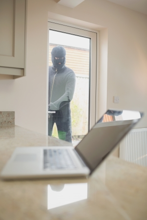 Burglar looking at laptop through the window of kitchen