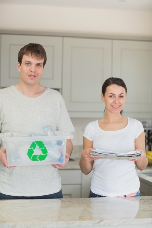 Smiling couple holding newspapers and recycling bin in kitchen photo