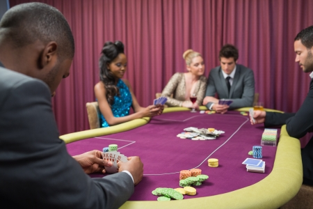 Man looking at his poker cards in game at casino Stock Photo - 20517488
