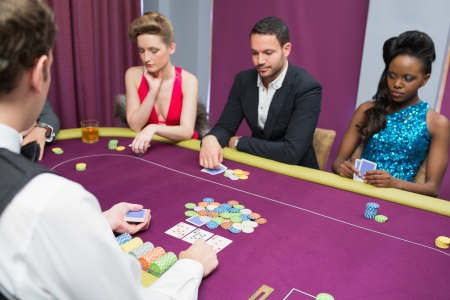 Man and two women playing poker waiting for the dealer at the casino Stock Photo - 20517430