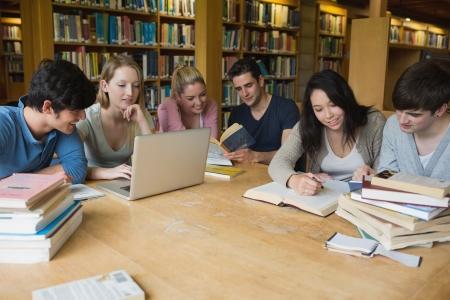 Studenten zitten aan een tafel in een bibliotheek, terwijl het leren en werken op een laptop Stockfoto
