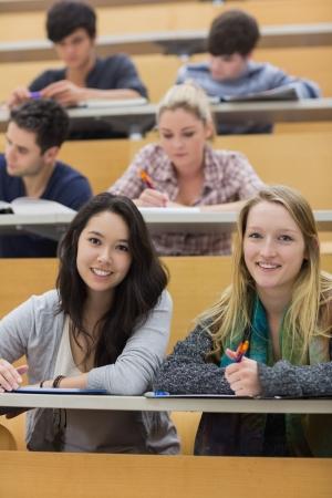 taking note: Sorridente studenti seduti in una sala di lettura mentre si scrivono note Archivio Fotografico