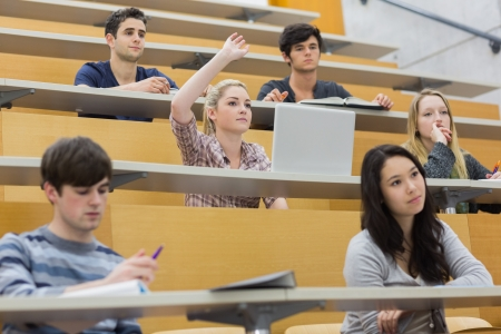 Students taking an active part in a lesson while sitting in a lecture hall photo
