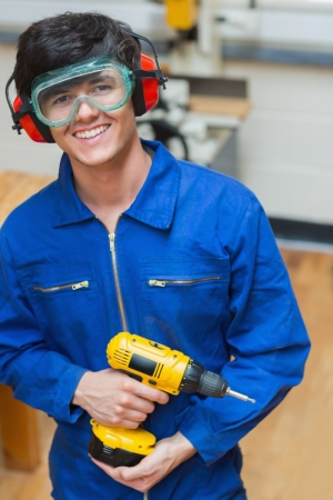 boiler suit: Smiling student standing in a woodwork class and holding a driller