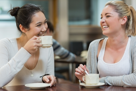 Two students having fun while sitting in college coffee shop and drinking coffee photo