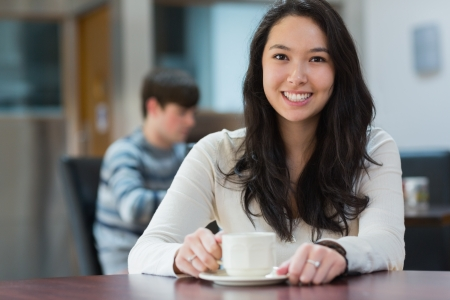 Happy student sitting in a coffee shop and drinking a cup of coffee while relaxing photo