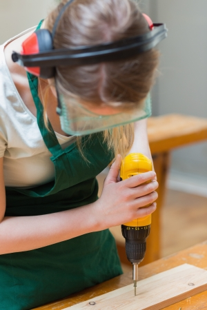 Student standing in a woodworking class and drilling a hole in a wooden board photo