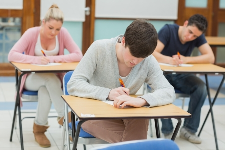 Three students sitting in a classroom at a desk and writing  Stock Photo - 20517286