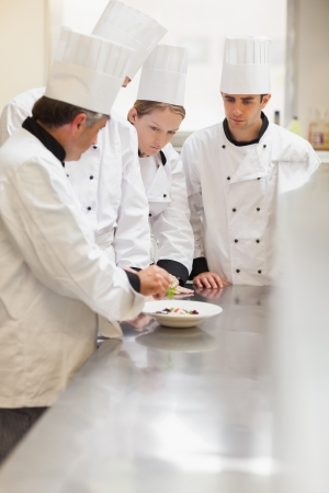 Trainees listening to the head chef in the kitchen at culinary school photo