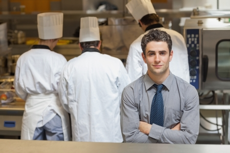 Waiter standing in a busy kitchen with three chefs behind him photo
