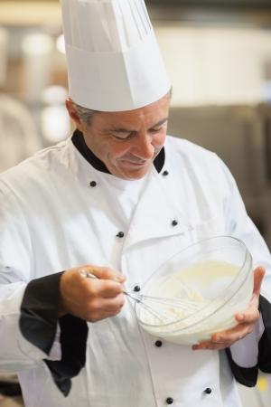 whisking: Chef whisking cream in the kitchen Stock Photo