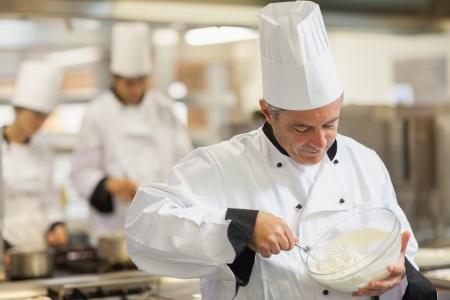 whisking: Happy chef whisking cream in kitchen
