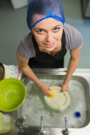 Smiling woman looking up from washing up in the restaurant Stock Photo - 20517462