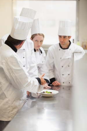 Head chef explaing something to class in kitchen photo