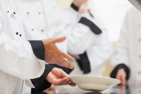 trainees: Head chef showing class a bowl in the kitchen on a counter Stock Photo