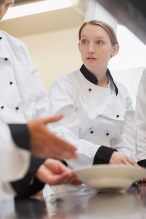Trainee chef listening to teacher in culinary school photo