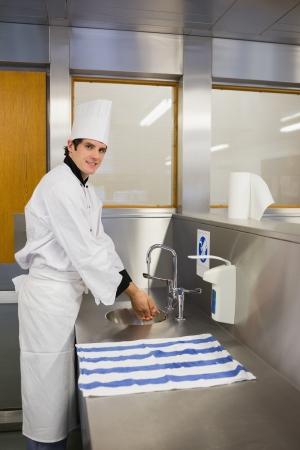 hygi�ne alimentaire: Chef de sourire se laver les mains dans le restaurant