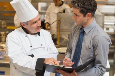 cocinero: Camarero y chef discutir el men� en la cocina