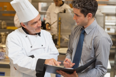Waiter and chef discussing the menu in the kitchen
