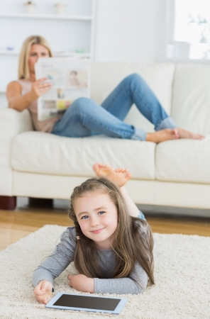Smiling little girl using tablet on living room floor while her mother is reading newspaper on the couch photo
