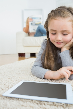 Little girl happily using tablet on the carpet with her mother reading the newspaper on the couch  photo