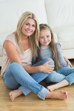 cherishing: Mother embracing her daughter while sitting on the floor  Stock Photo