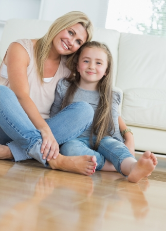 barefeet: Smiling mother and daughter embracing on living room floor