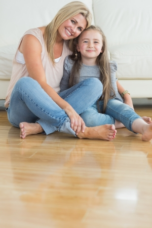 Mother and daughter sitting on the floor embracing in the living room photo