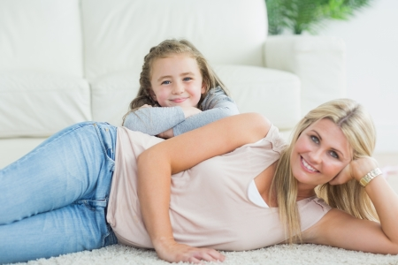 Daugher and mother relaxing together on the living room floor Stock Photo - 20501884