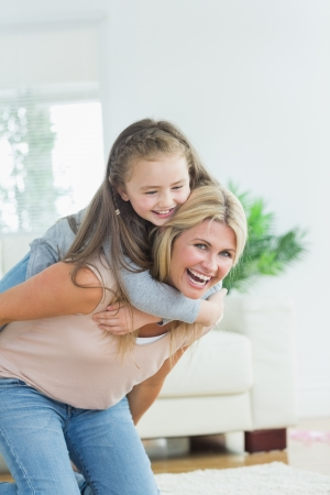 Laughing mother giving daughter a piggy bank in the living room Stock Photo - 20550966