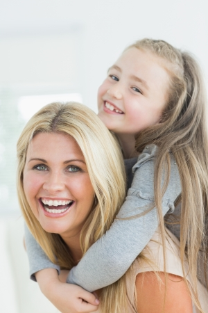Laughing mother and daughter on her mothers back Stock Photo - 20493704