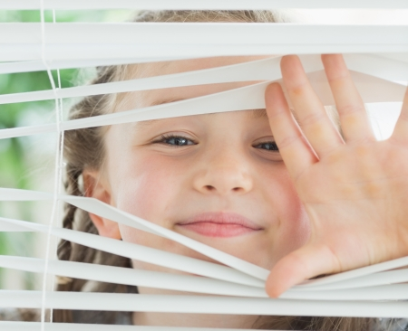 blind people: Smiling girl looking through the white window blinds  Stock Photo