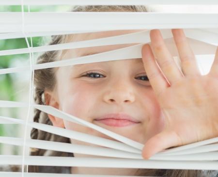 při pohledu na fotoaparát: Usmívající se dívka dívá přes bílé žaluzie Reklamní fotografie