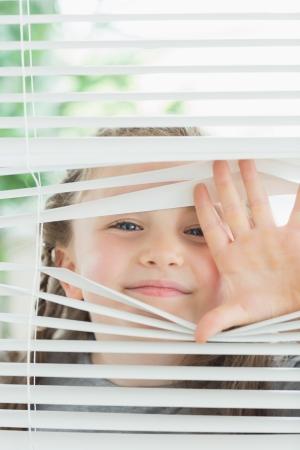 窓のブラインドを覗く幸せな子