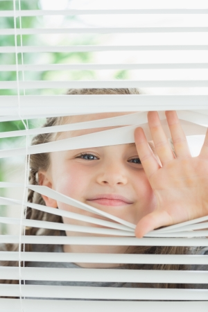 blind child: Happy child peeking through window blinds