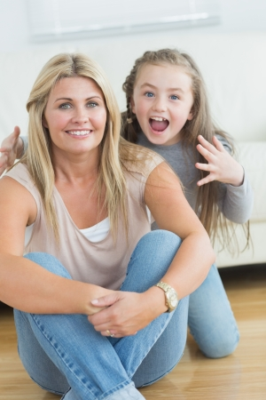 Little girl about to giver her mother a fright on floor of living room Stock Photo - 20550970