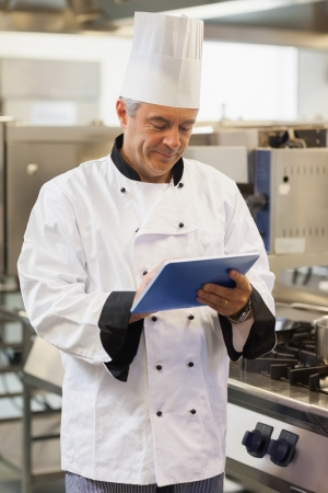 Chef using his digital tablet in the kitchen photo