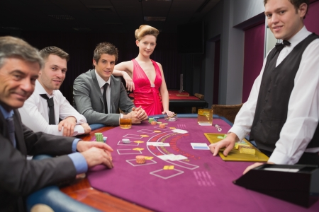 People sitting at blackjack table and smilng in the casino photo