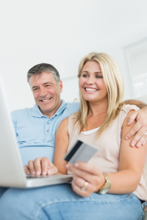 Husband and wife shopping online with laptop on the sofa photo